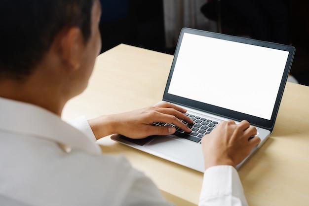 Деловой человек или офисный работник с помощью портативного компьютера, сидя за столом.