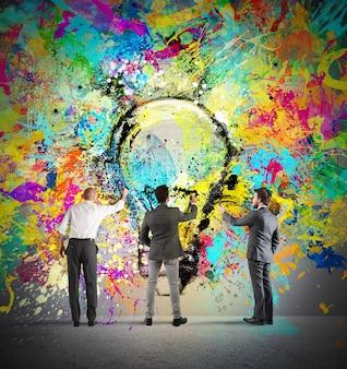 Деловой человек вместе раскрашивает большую цветную лампочку на стене