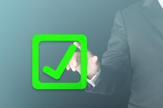 사업가는 체크박스에 손가락으로 누르는 가상 녹색 확인 표시를 사용하여 좋은 결정으로 승인된 비즈니스 진행률이 검증된 개념을 확인했습니다. 프리미엄 사진