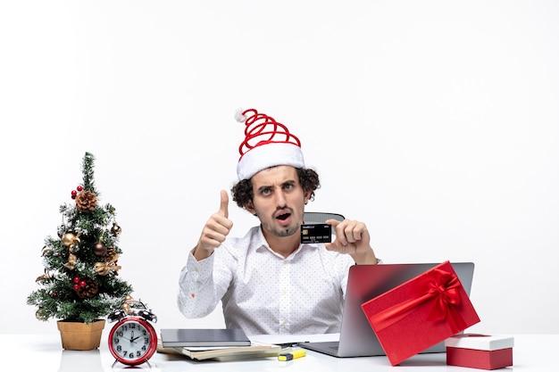 サンタクロースの帽子をかぶって、オフィスで彼の銀行カードを見て質問をしているビジネスパーソン