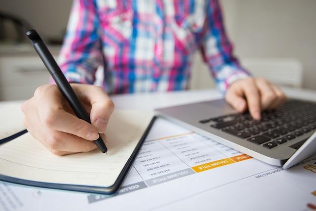 Деловой человек, работающий на ноутбуке и делающий заметки