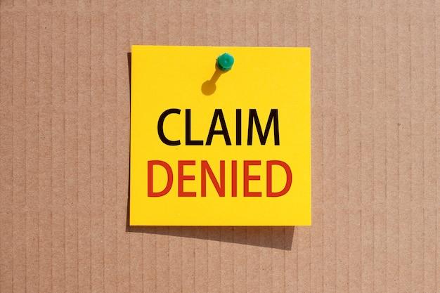 Деловая фраза - претензия отклонена - написана на желтой квадратной бумаге и прикреплена булавками к картону.