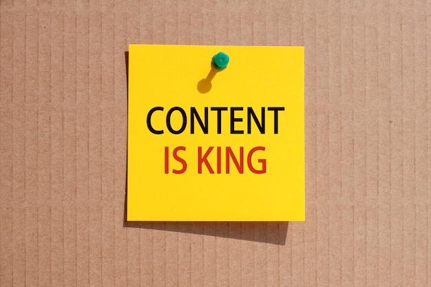 비즈니스 문구-콘텐츠는 왕입니다-노란색 정사각형 종이에 작성하고 판지, 개념에 고정