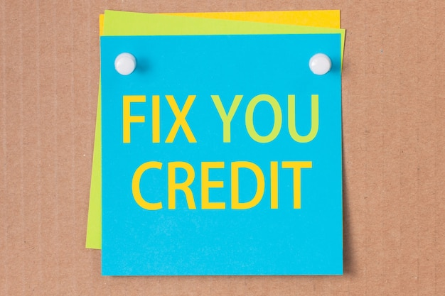 Business phrase - fix you credit - written on blue square sticker and pinned on paperboard