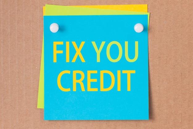 Деловая фраза - исправь кредит - написана на синей квадратной наклейке и прикреплена к картону