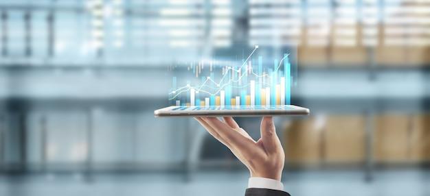 Рост графика бизнес-плана и увеличение положительных показателей графика в его бизнесе, планшет в руке