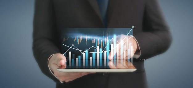 事業計画グラフの成長と彼のビジネスにおけるチャートの肯定的な指標の増加、タブレットを手に