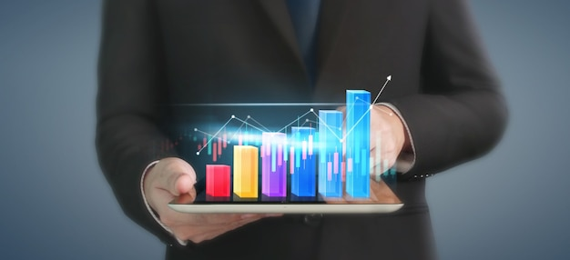 Business plan graph growth and increase of chart positive indicators in his business, tablet in hand