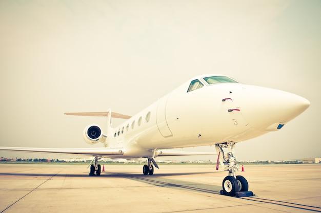 Бизнес-самолет, припаркованный в аэропорту - эффект ретро-винтажного фильтра