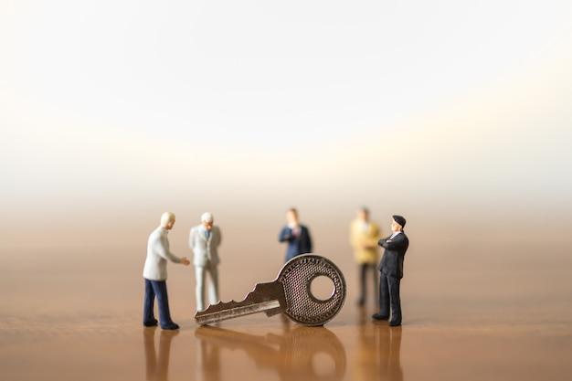 ビジネス、計画、セキュリティの概念。ビジネスマンのミニチュアのグループは、人々が立っているとコピースペースを持つ木製のテーブルの上の銀の鍵との出会いを数字します。