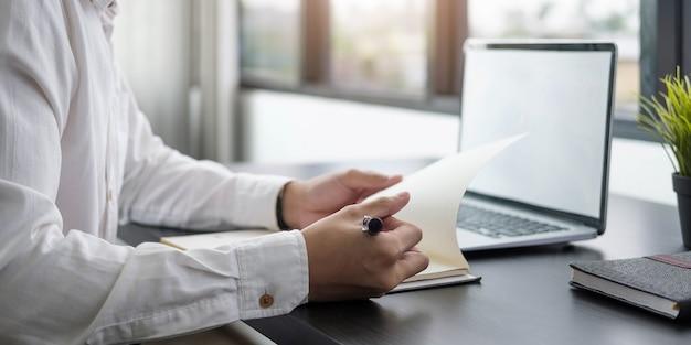 Бизнес-планирование, деловой человек, писать на ноутбуке и работать на портативном компьютере в современном офисе. человек изучает онлайн-курс через ноутбук и читает лекцию в блокноте