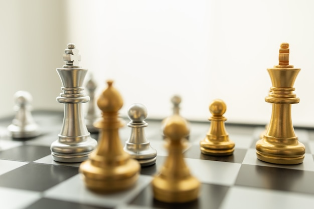 Business and planning concept. closeup of king silver and gold chess pieces on cheseboard with other chess piece with copy space.