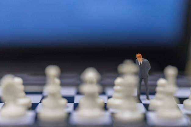 Концепция бизнес-планирования. крупным планом бизнесмен миниатюрная фигура людей, стоящих на шахматной доске с шахматными фигурами