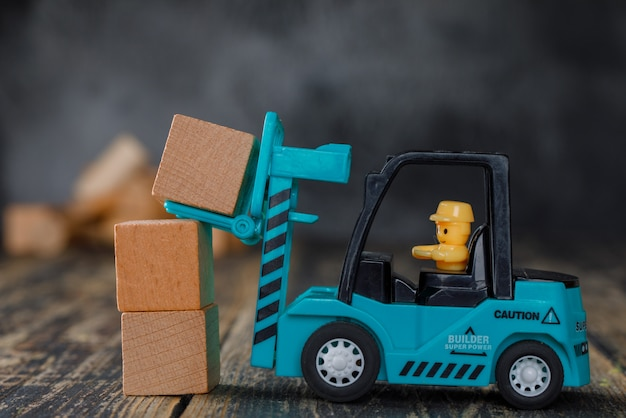 Business planning concept side view. forklift truck stacking wooden blocks.