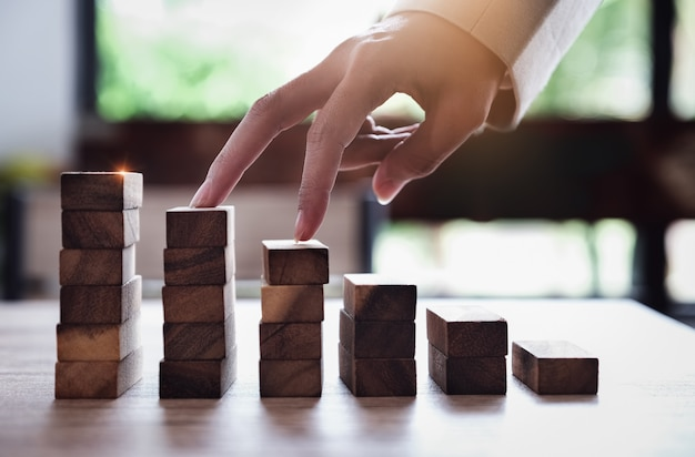 Business planning and growth concepts, a business man uses his finger to climb up the wooden blocks
