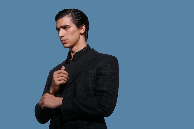 Деловой портрет красивого подходящего молодого человека в черном костюме устраивает ее рукав на синем фоне. горизонтальный вид.