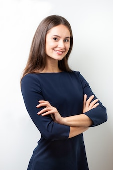 白い壁に青いオフィスのドレスを着た女性のビジネスの肖像画。
