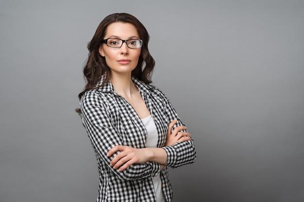 眼鏡をかけた魅力的なブルネットの若い女性のビジネスの肖像画は、彼女を横切るカメラを見る