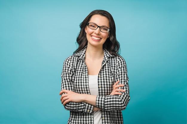 眼鏡をかけた笑顔のブルネットの若い女性のビジネスの肖像画は、彼女の腕のカメラを見てください