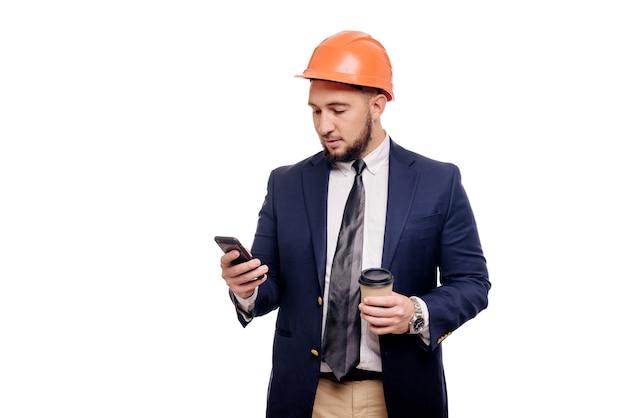 Деловой портрет удивленного подрядчика и разработчика, говорящего о телефоне. бизнесмен в каске с чашкой кофе, стоящей на белом фоне. новости и концепция кофе-брейка