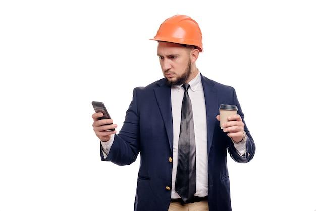電話について話している、驚いた請負業者と開発者のビジネスの肖像画。白い背景の上に立っているコーヒーのカップとヘルメットをかぶったビジネスマン。ニュースとコーヒーブレーキのコンセプト