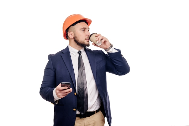 Business portrait of surprised contractor and developer, talking about phone. businessman in hard hat with cup of coffee standing over white background. news and coffee brake concept