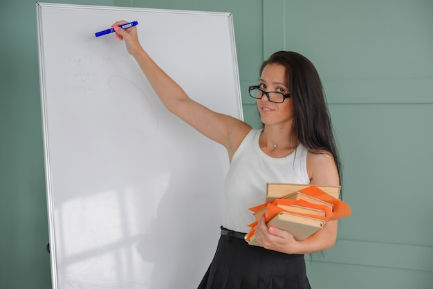 Рисуя на доске бизнес-презентацию, тренер проводит урок для учеников.