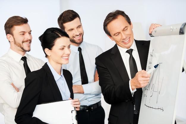 Деловая презентация. уверенный зрелый бизнесмен, указывая на график на доске и улыбаясь, пока его коллеги стояли рядом с ним и смотрели на эскиз