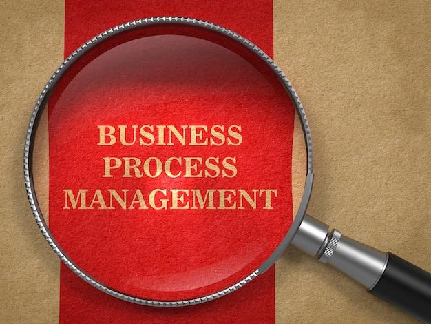 ビジネスプロセス管理の概念。赤い縦線のある古い紙の虫眼鏡。