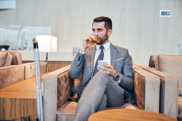 Business professional swallowing some whisky while working on a phone