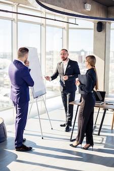 ビジネスの専門家。若い成功したビジネスマンのグループは、新しい近代的なオフィスで時間を過ごしながら、グラフを使用してデータを分析しています。