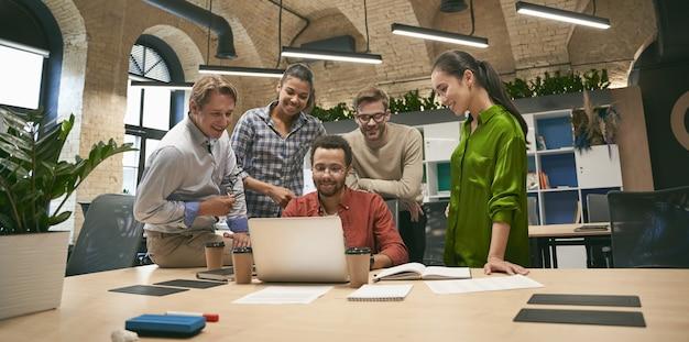 Бизнес-профессионалы на работе, мультикультурная команда молодых веселых деловых людей, анализирующих