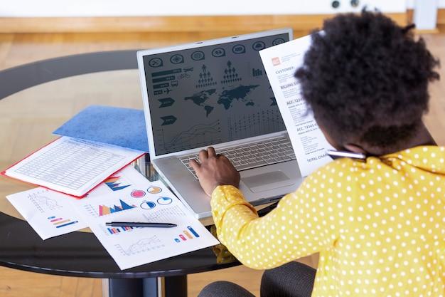 ビジネスの専門家。ビジネスの女性がオフィスで時間を過ごしながらコンピューターを使用してデータを分析