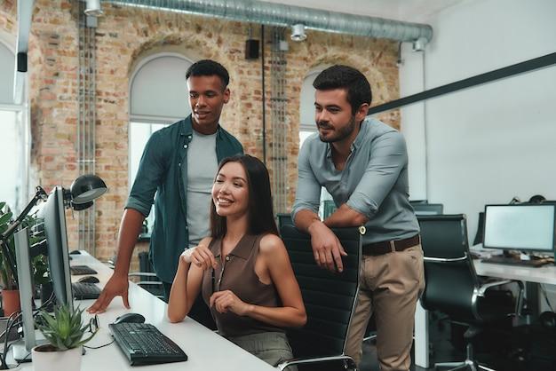 젊고 쾌활한 3명의 비즈니스 전문가 그룹은 새로운 프로젝트에 대해 논의하고 찾고 있습니다.