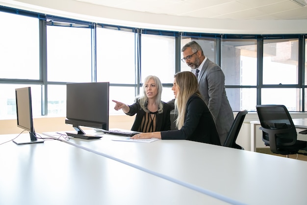 Business professionals watching presentation on computer monitor together, discussing project, sitting at workplace and pointing at display. business communication or teamwork concept