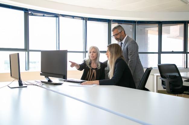 コンピューターのモニターで一緒にプレゼンテーションを見たり、プロジェクトについて話し合ったり、職場に座ったり、ディスプレイを指さしたりするビジネスプロフェッショナル。ビジネスコミュニケーションまたはチームワークの概念
