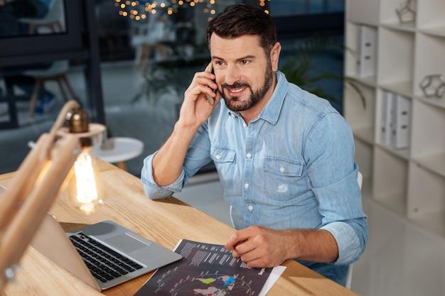 ビジネスプロジェクト。彼の耳に電話を置き、仕事について話している間彼のビジネスパートナーと話すハンサムな素敵なインテリジェントビジネスマン