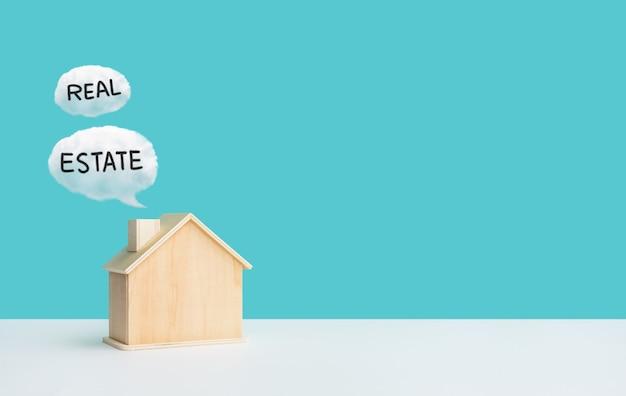 Концепции бизнес-недвижимости с модельным домом и текстом о недвижимости, финансовом или банковском