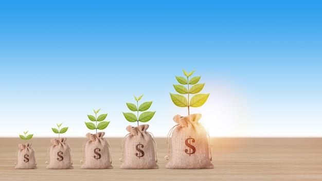 Business property investment concept, money bag with plant growing and stacking coins saving growth on wooden desk on blue background studio for financial real estate advertising concept