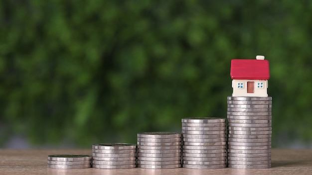 Business property investment house and stacking coins saving growth on wooden desk and green background for financial real estate advertising concept