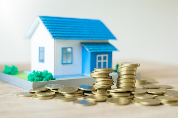 Business real estate concept house model with coins stack on wooden table and bokeh in background
