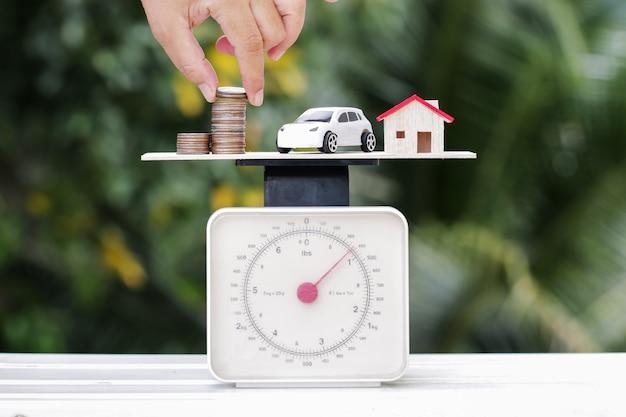 ビジネス不動産投資の概念:ウッドグリーンの背景に体重計の手ドロップシッピングマネーコイン。リスクの世界での貯蓄貸付/住宅ローン新築住宅車スポンサーシップリースクレジット