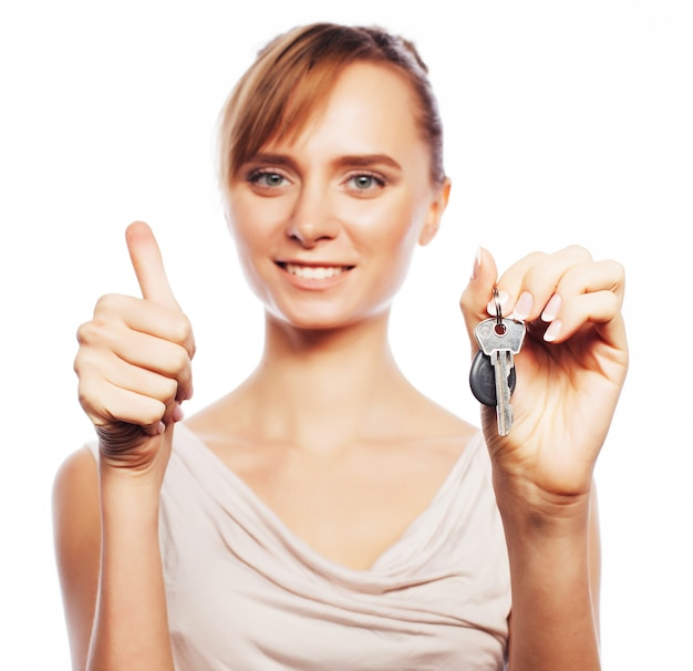 Business, real estate and office concept: young businesswoman with key. positive emotion. isolated on white.