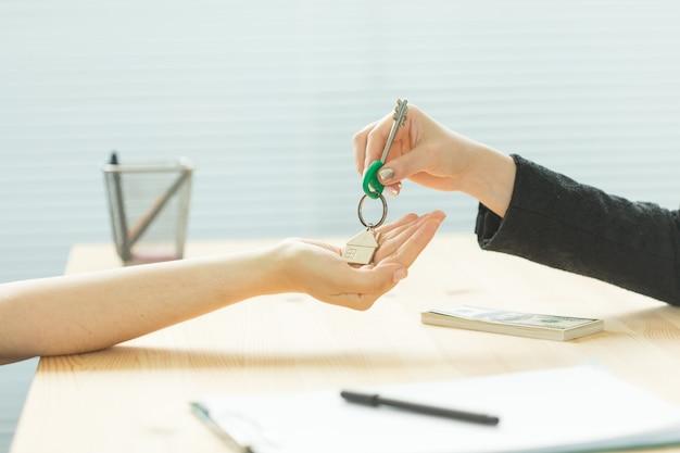 Концепция бизнеса, риэлтора и недвижимости - ключи из рук в руки от нового дома