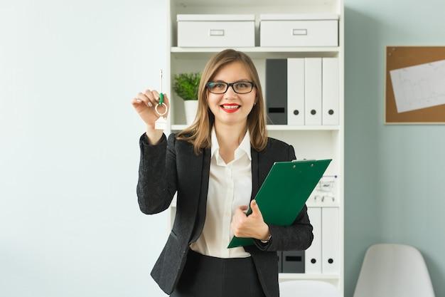 Бизнес, риэлтор и концепция недвижимости - портрет привлекательной улыбающейся женщины, держащей ключи