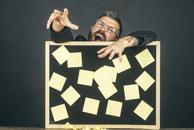 비즈니스 알림 메모 관리 고용 개념 정장에 쾌활 한 수염된 남자가 보드를 보유 하고있다