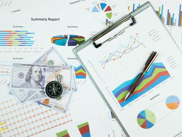 Диаграмма бизнес-отчета и анализ финансового графика с долларовыми деньгами, ручкой и компасом на столе