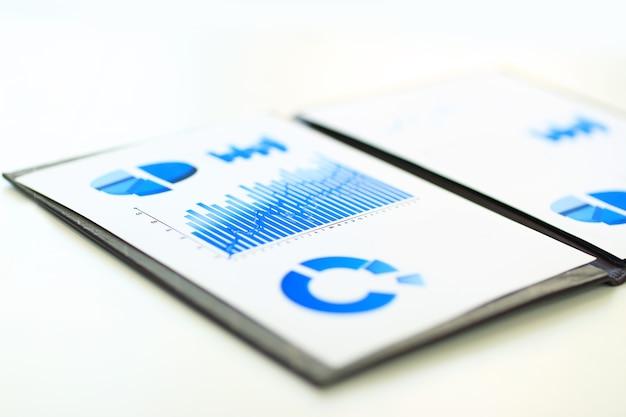 ビジネスマンの作業ディレクトリにある財務およびマーケティングスケジュールを含むビジネスレポート