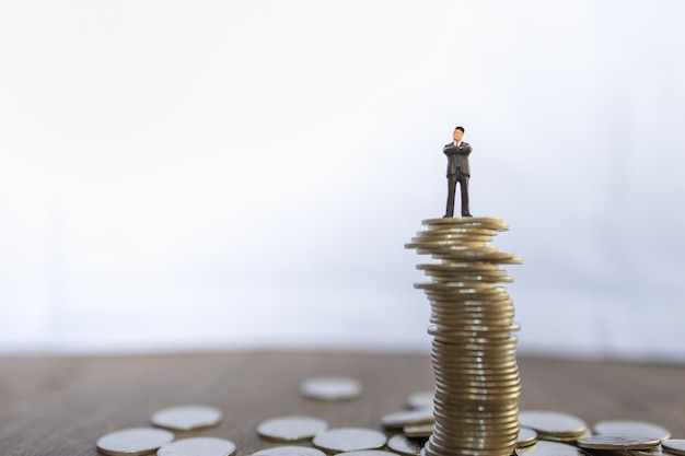 Business, risk, investment and saving concept.  close up of businessman miniature people figure standing on top of unstable stack of coins with copy space.
