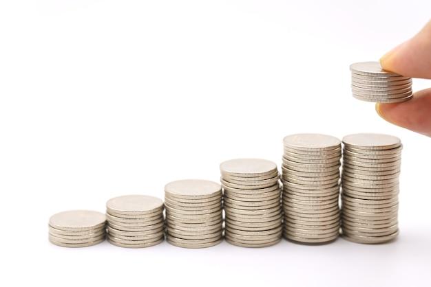 비즈니스, 저축 및 금융 개념입니다. 동전 더미를 들고 있는 남자 손가락을 닫고 흰색 배경에 은화 더미 위에 올려 놓습니다.